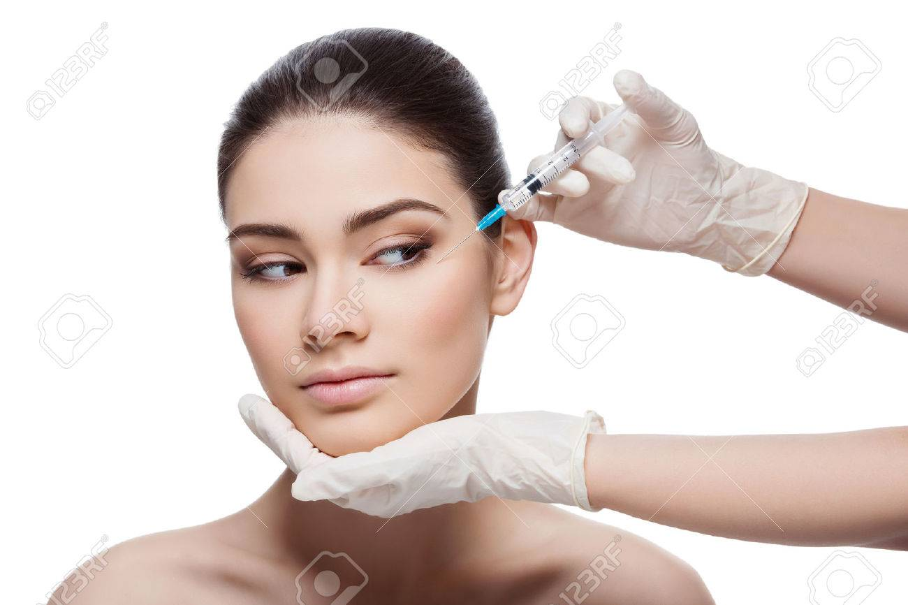 Beautiful young woman gets beauty injection in eye area from sergeant. Isolated over white background. - 47856028