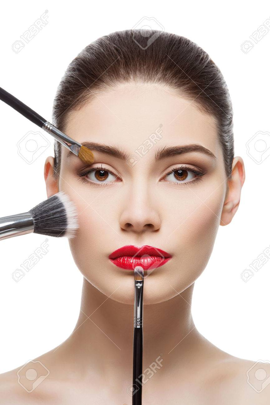 Closeup portrait of beautiful young woman with makeup brushes. Red lips. Isolated over white background. - 49142021