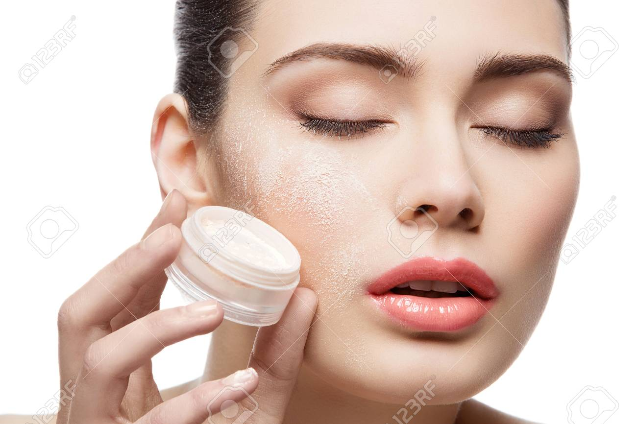 Beautiful young woman holding jar with loose powder near face. Closed eyes. Macro. Isolated over white background. Copy space. - 49142022
