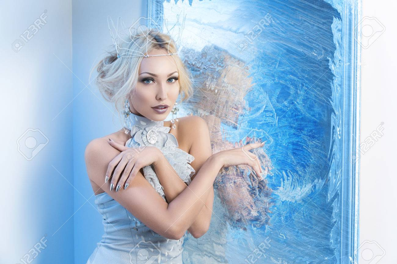 Beautiful young woman in crown and silver top standing near frozen mirror. Snow queen. Copy space. - 49142323