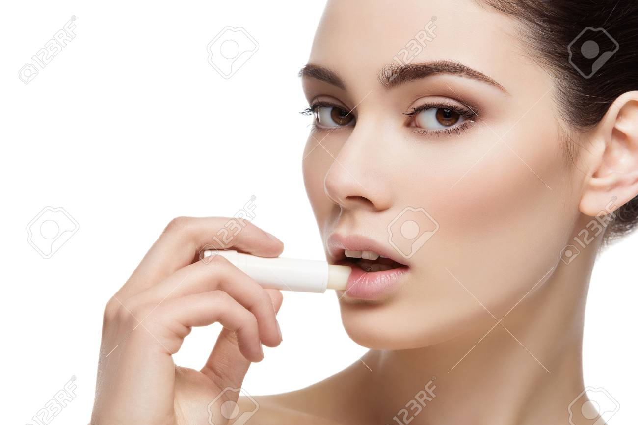 Beautiful young woman applying chapstick to lips. Isolated over white background. Copy space. - 51170135