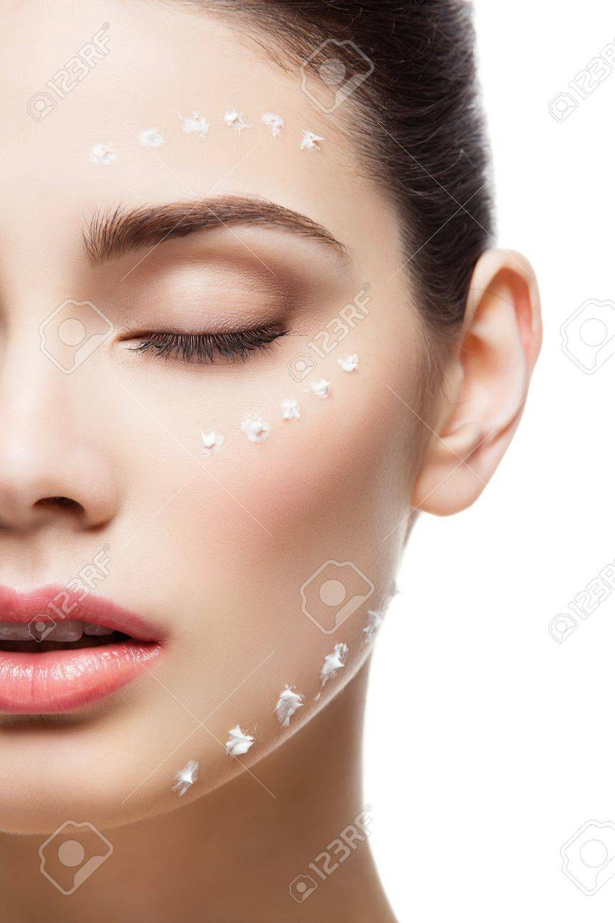 Beautiful young woman with moisturizing cream dots on face. Isolated over white background. Copy space. - 52240418