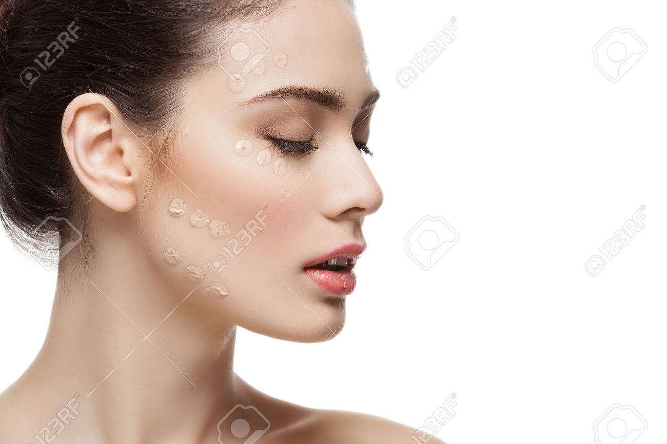 Beautiful young woman with foundation cream on face. Beauty shot. Isolated over white background. Copy space. - 52240426