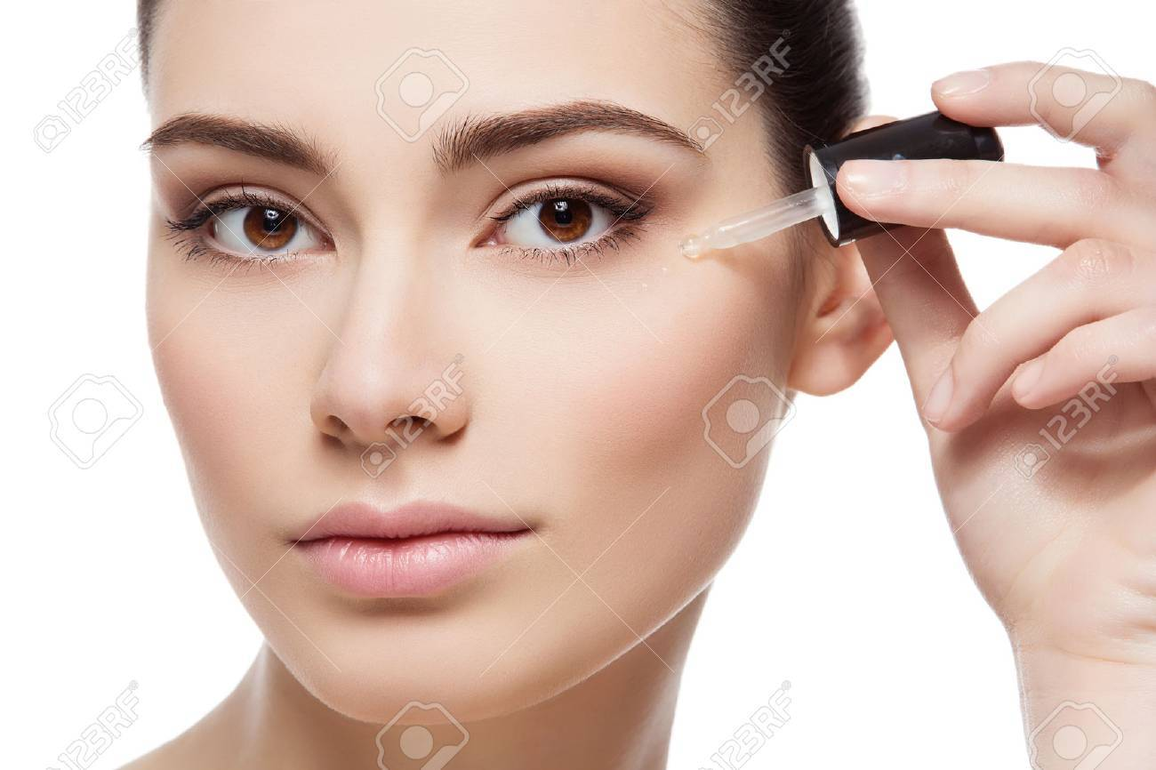 Beautiful young woman applying serum moisturizer on under eye area. Beauty shot. Close-up. Isolated over white background. - 52484745
