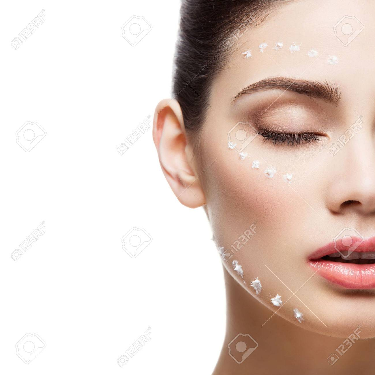 Beautiful young woman with moisturizing cream dots on face. Isolated over white background. Copy space. Square composition. - 55740326