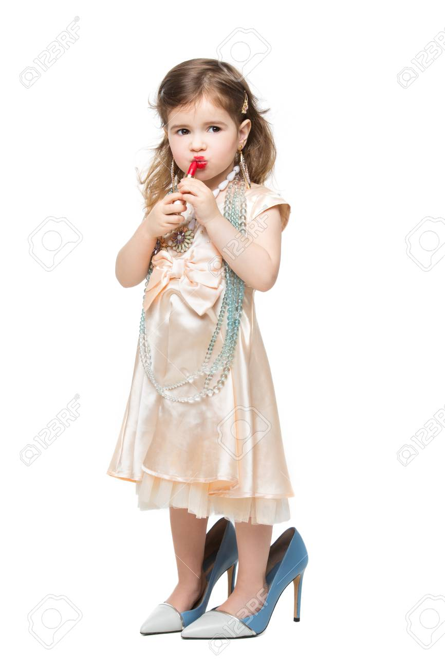 ce422523a56ca5 Mooi klein meisje in jurk en moeders hoge hakken die rode lippenstift.  Geïsoleerde over witte