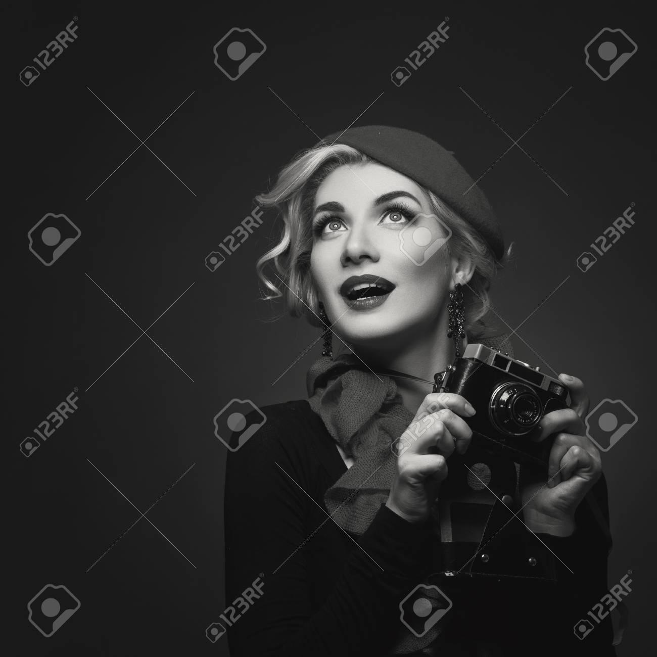 f09a96b665da 60246678-giovane-e-bella-donna-in-berretto-rosso -in-possesso-di-macchina-fotografica-retrò-espressione-sorpresa-.jpg