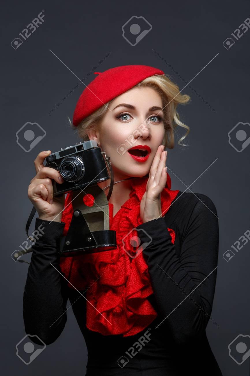 f016b825b4d2 60904810-giovane-e-bella-donna-in-berretto-rosso -in-possesso-di-macchina-fotografica-retrò-espressione-sorpresa-.jpg