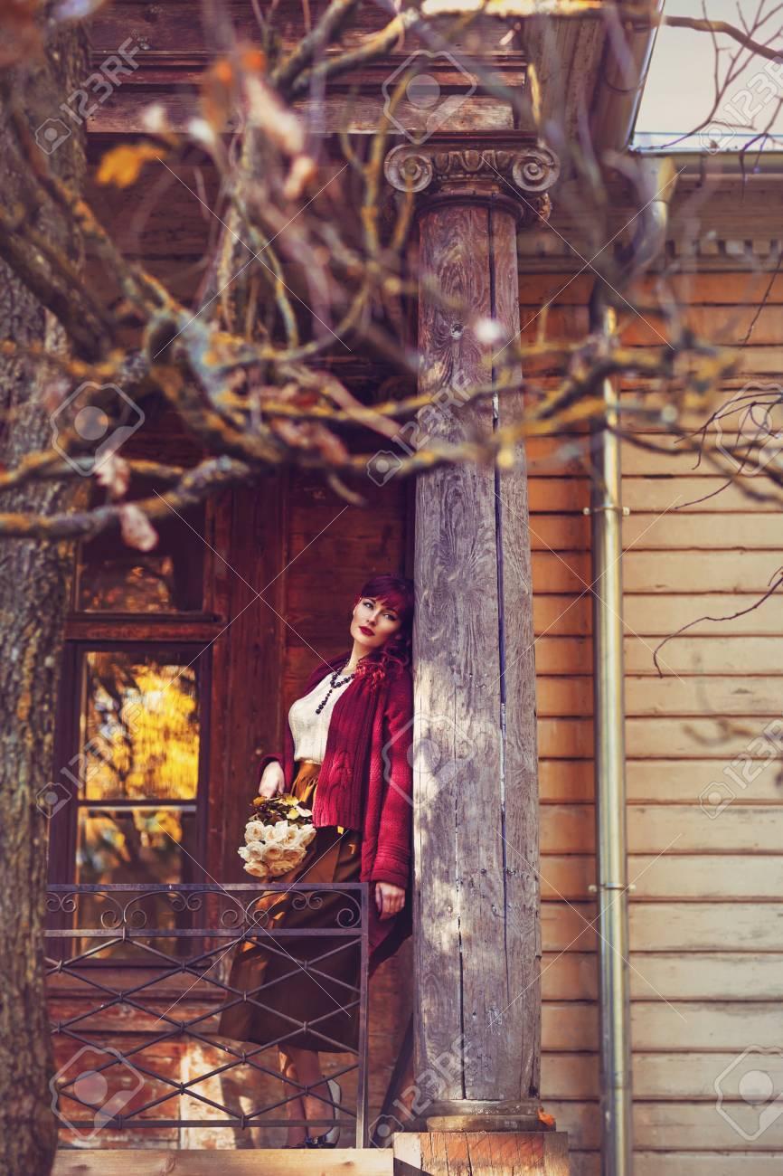 Banque d images - Belle jeune femme en jupe longue et écharpe en laine  rouge debout sur le vieux balcon de la maison. Début de l automne. tir  extérieur. a3f2d32dada
