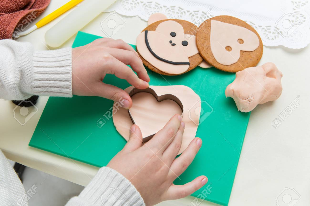 61766727-children-hands-making-funny-christmas-gingerbread-monkey-head-shape-cookies.jpg