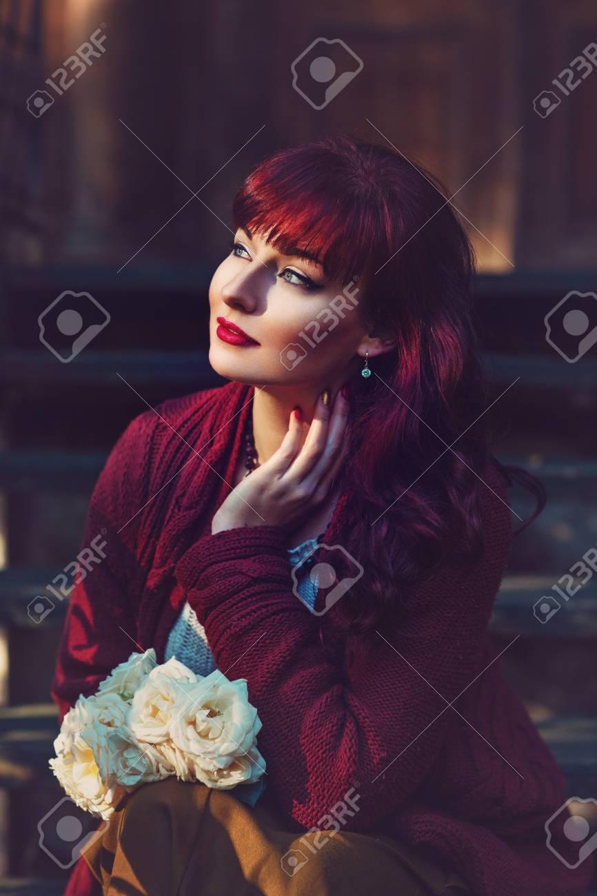 Banque d images - Belle jeune femme en jupe longue et écharpe en laine  rouge assis sur vieil escalier maison tenant des fleurs. 43efa648460