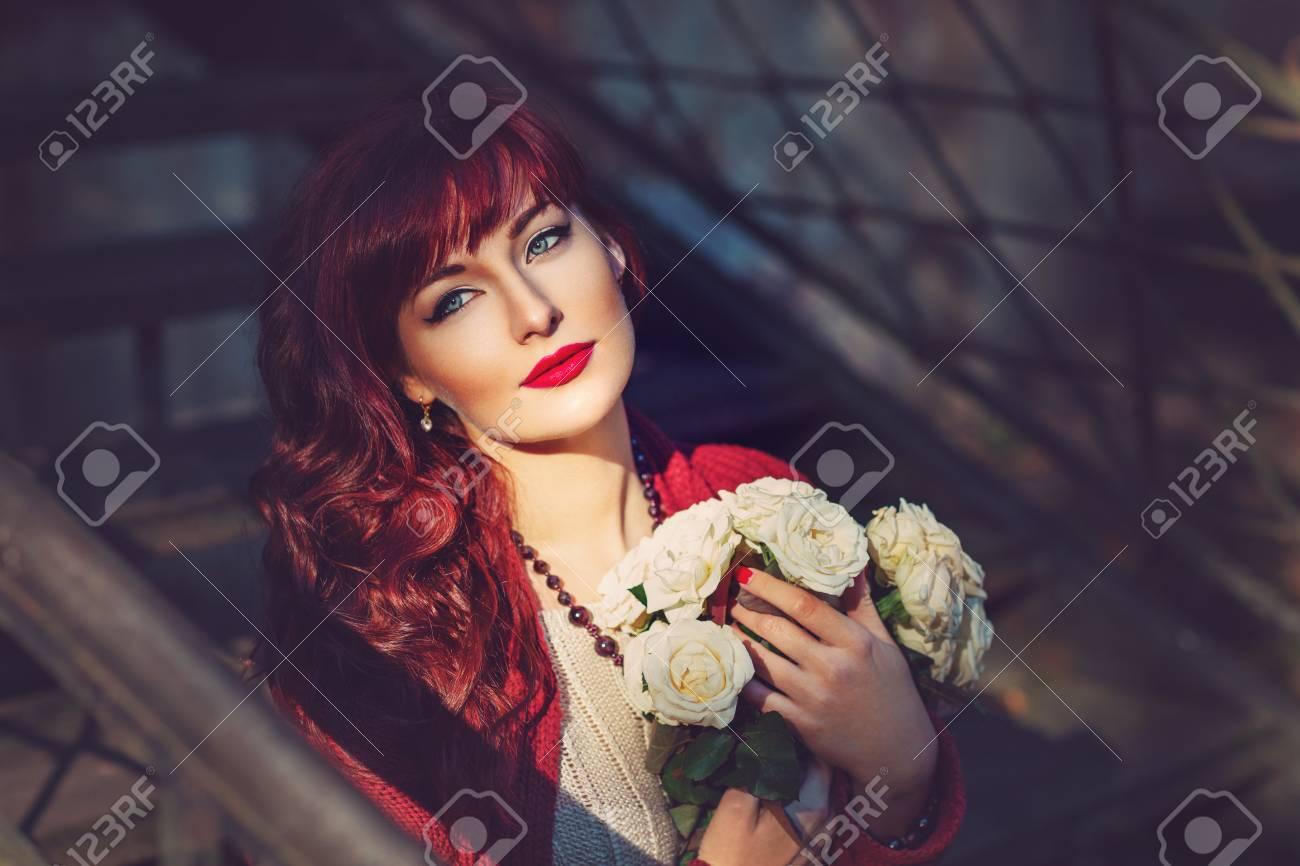 Banque d images - Belle jeune femme en laine rouge écharpe assis sur les  escaliers de la vieille maison tenant des fleurs. Début de l automne. 028a7979958