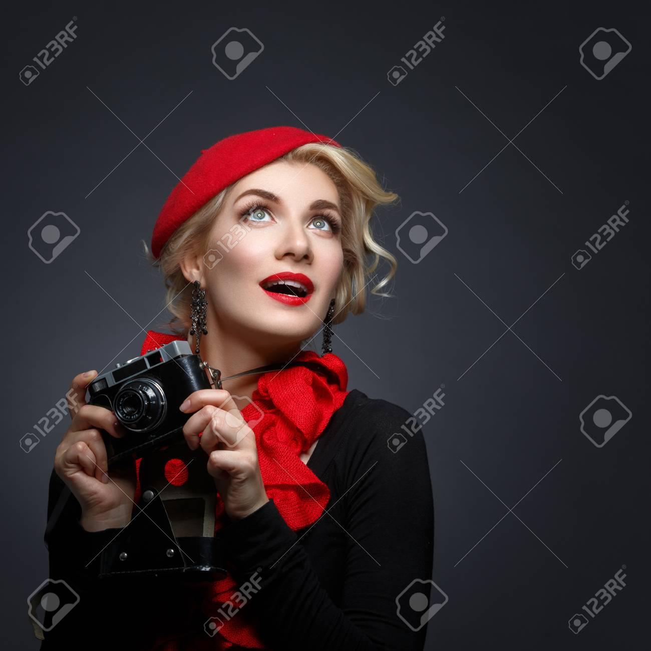 9c195ab38abb 62176193-giovane-e-bella-donna-in-berretto-rosso -in-possesso-di-macchina-fotografica-retrò-espressione-sorpresa-.jpg