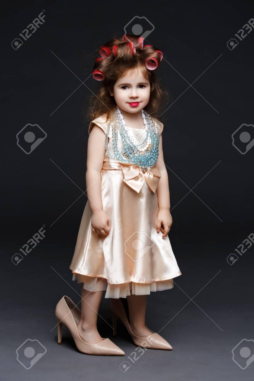 7eb7d05086d338 Leuk meisje in kleding en grote hoge hakken schoenen met rode lippen en  rollen in het