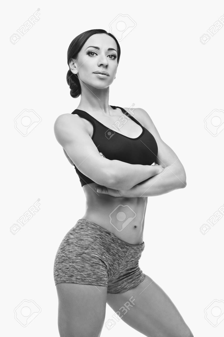 176beb4cfd Perfect body. Studio shot. Copy space. Monochrome. Beautiful fit muscular  young woman in sport bra and shorts isolated on white background. Perfect