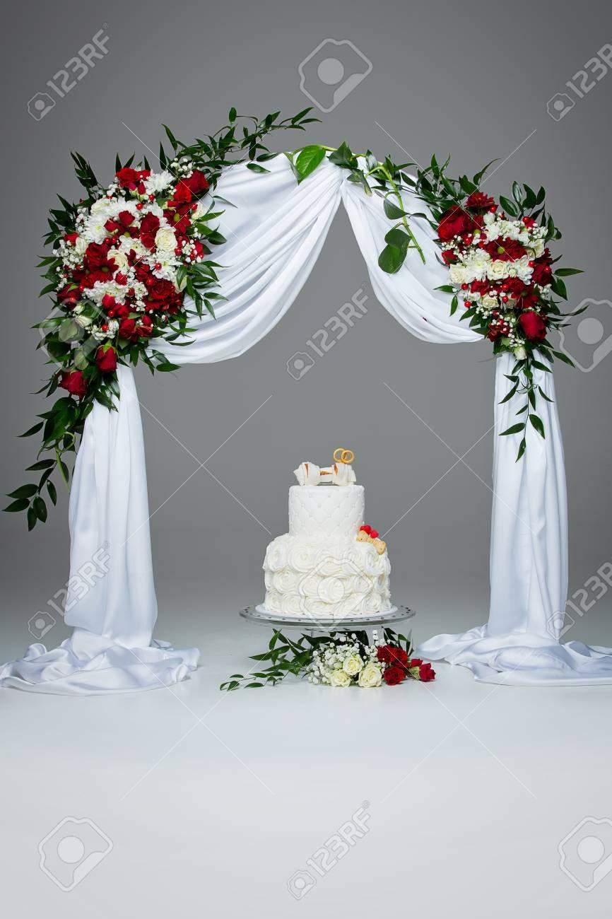 Hermoso Pastel De Bodas Blanco Tradicional Con Decoración De Hueso Para El Banquete De Boda De Perro De Pie Bajo Arco De Flores Tiro Del Estudio
