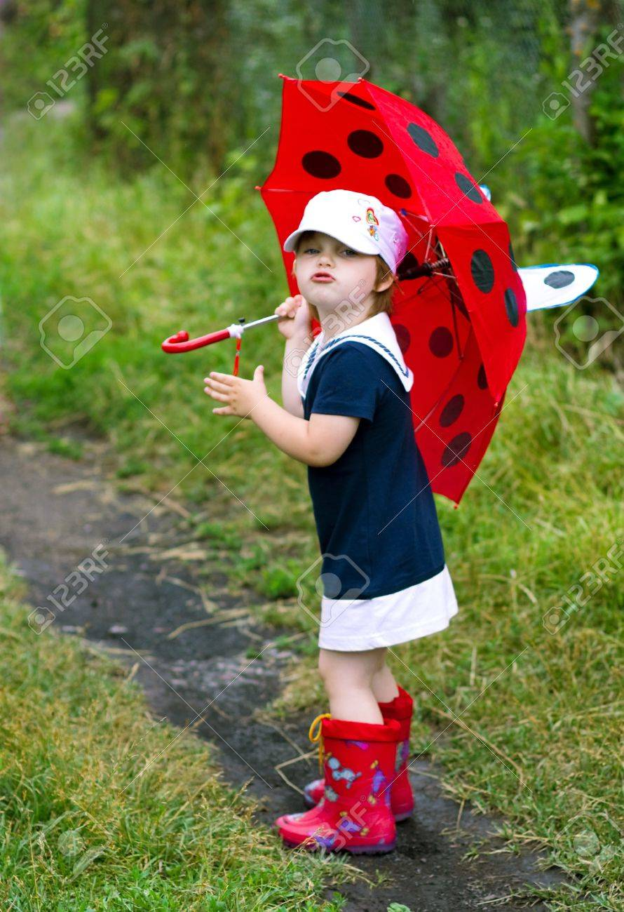 The little girl with an umbrella and in rubber boots Stock Photo - 10425690