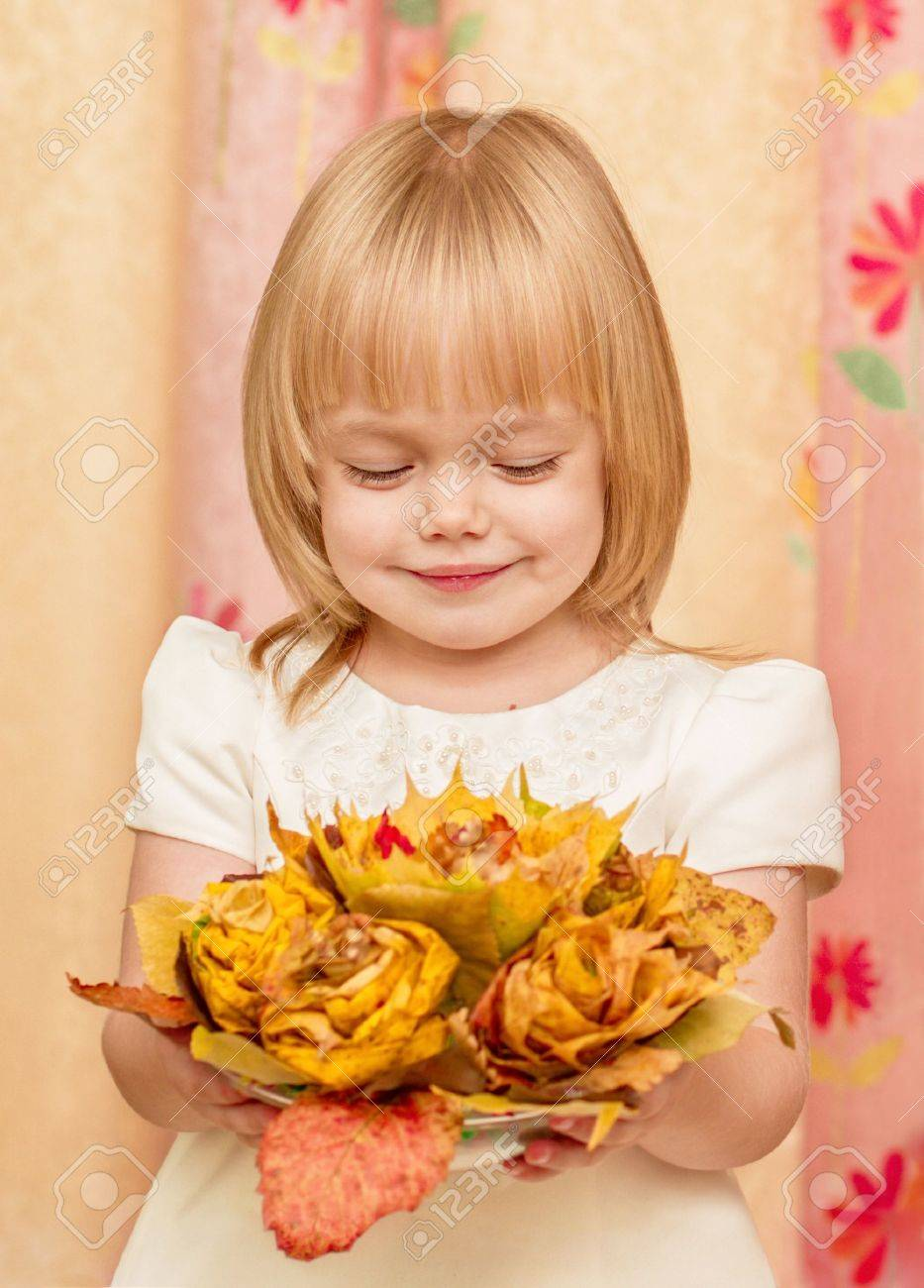 The little girl looks at the bouquet of autumn leaves Stock Photo - 15738537