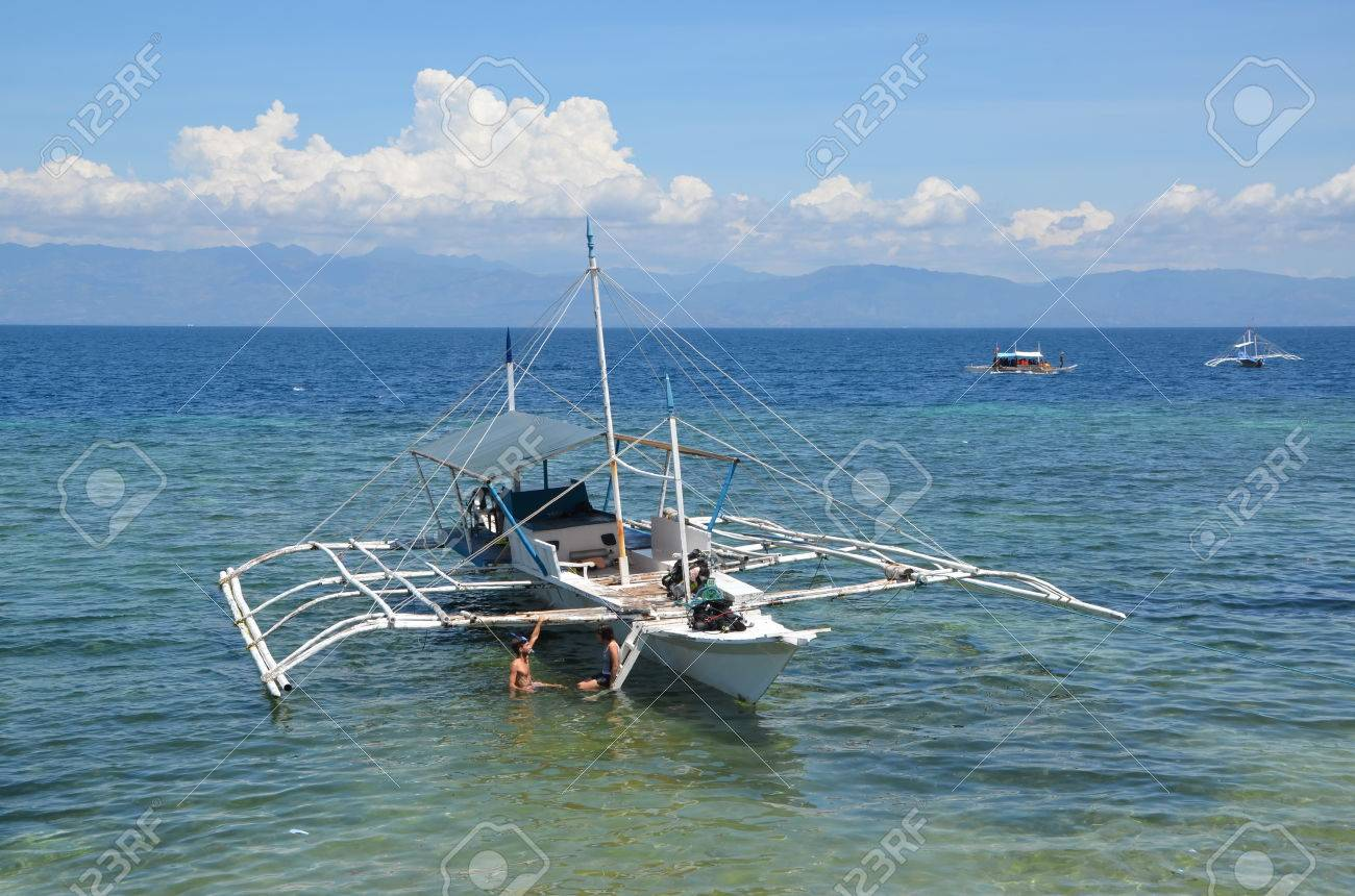 young couple at bangka boat in the ocean in moalboal philippines