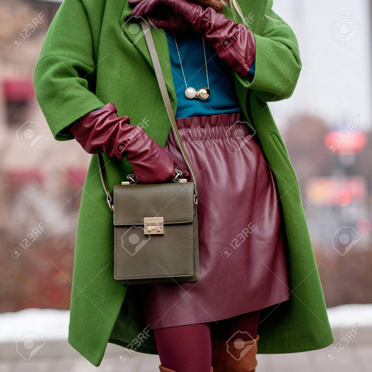 Street and bright style. Young girl in a green coat, stylish leather skirt. Details. Sguare image photo - 101515356