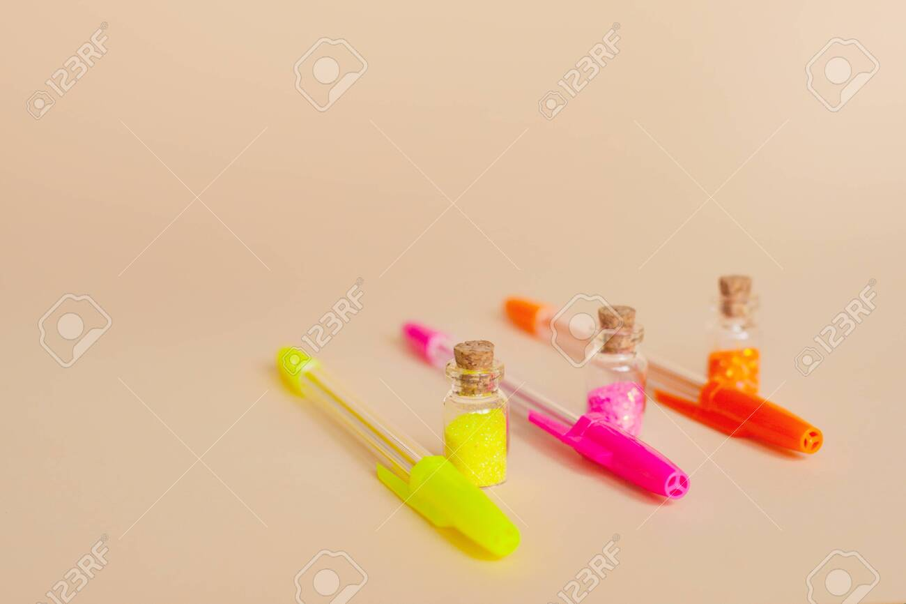 Colorful Glitter In Bottles And Bright Neon Pens For Writing