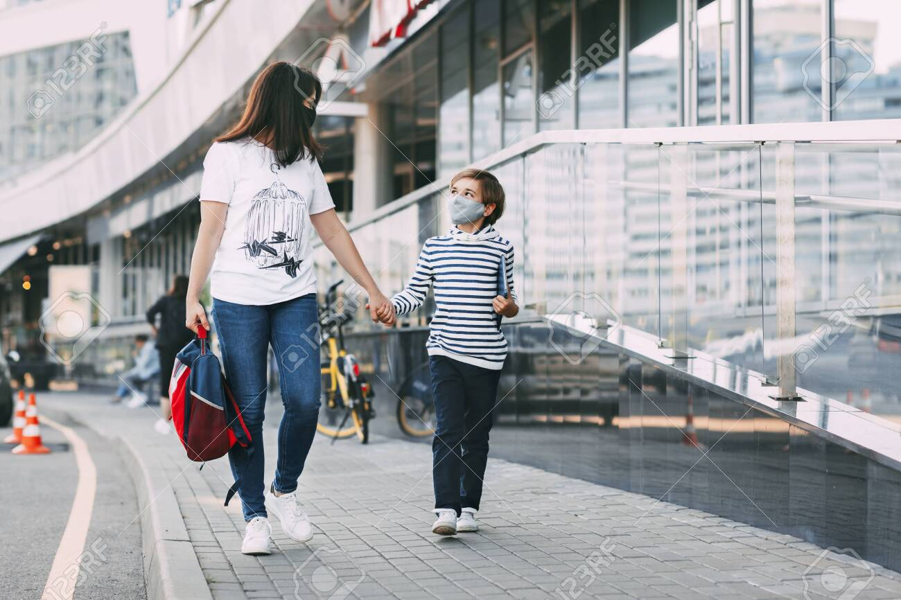 A young mother in a mask carries a backpack and accompanies her son to school or kindergarten. A boy with a tablet goes to school with his mother during the epidemic. Social distance - 151811592