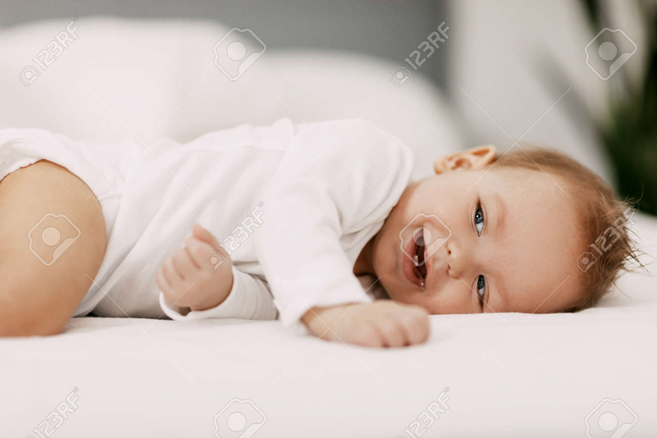 A blue-eyed baby lies in a snow-white bed under a blanket, laughs and indulges - 168313388