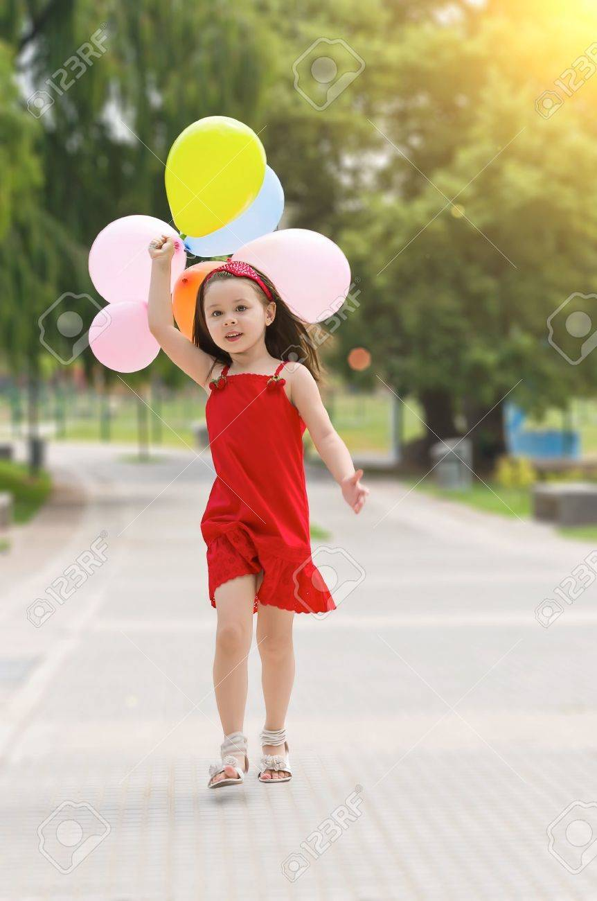 Happy girl with balloons walking on the park Stock Photo - 14690697