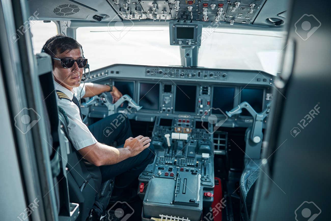 Smiling handsome pilot sitting in plane cockpit - 156980391