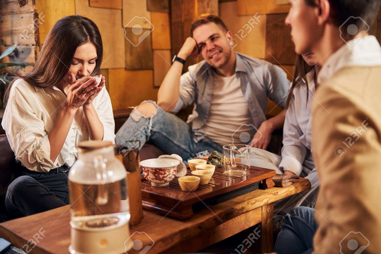 Charming young woman enjoying tea with friends in cafe - 165063906