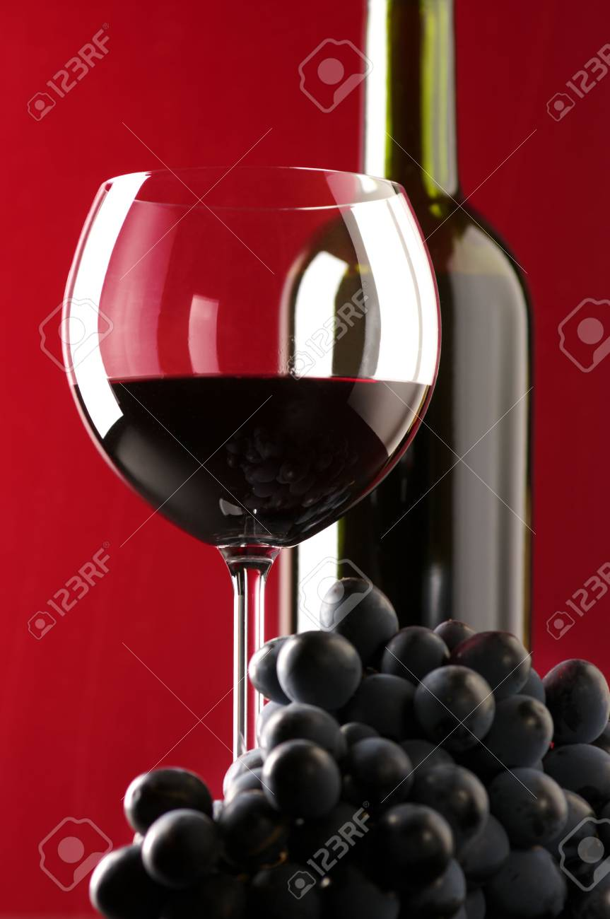 Glass of red wine, bootle and bunch of black grape on red background.. Stock Photo - 5612049