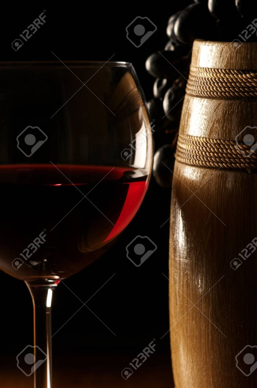 Glass of red wine close-up, dark grape and souvenir barrel on wooden surface. Stock Photo - 5864682