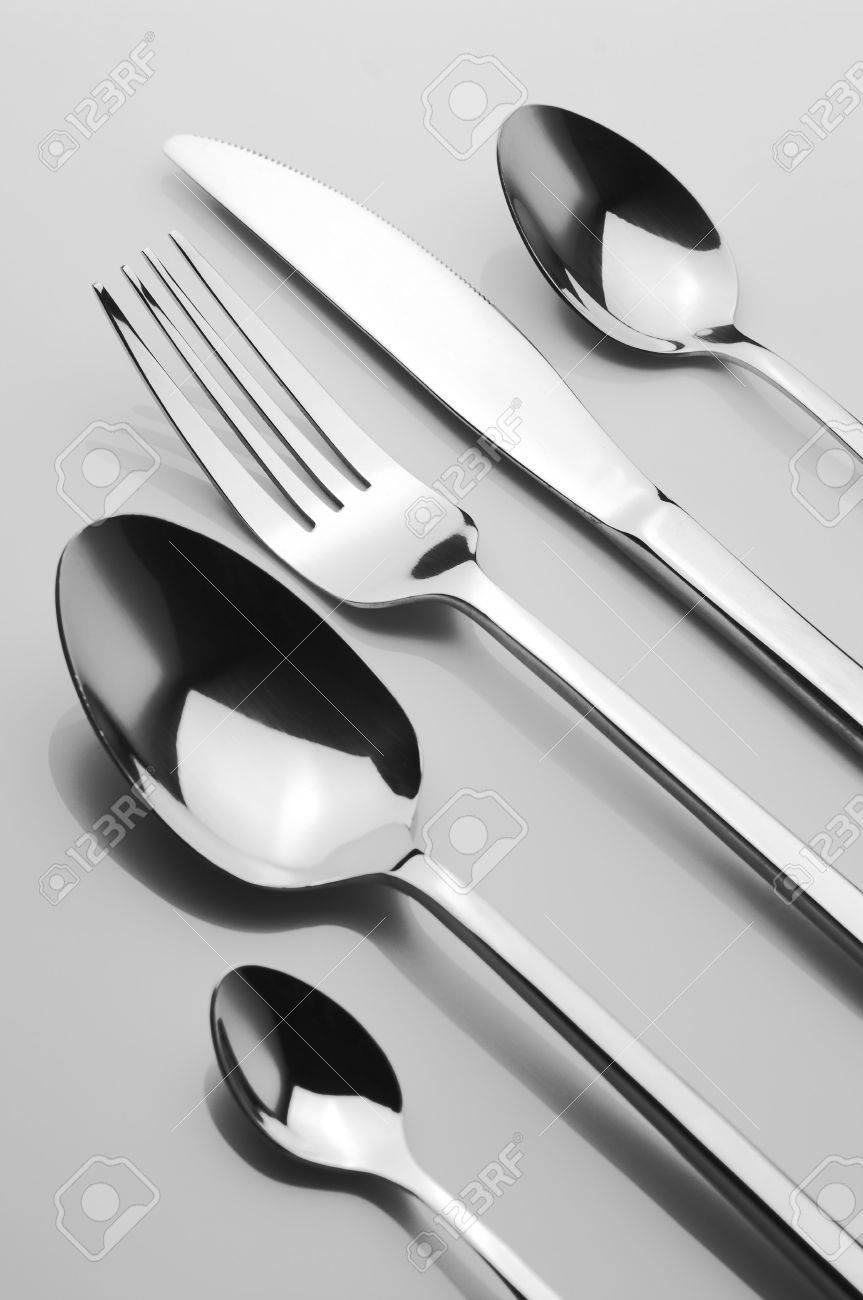 Set of stainless spoons, knife and fork on light background. B&W. Stock Photo - 6290766