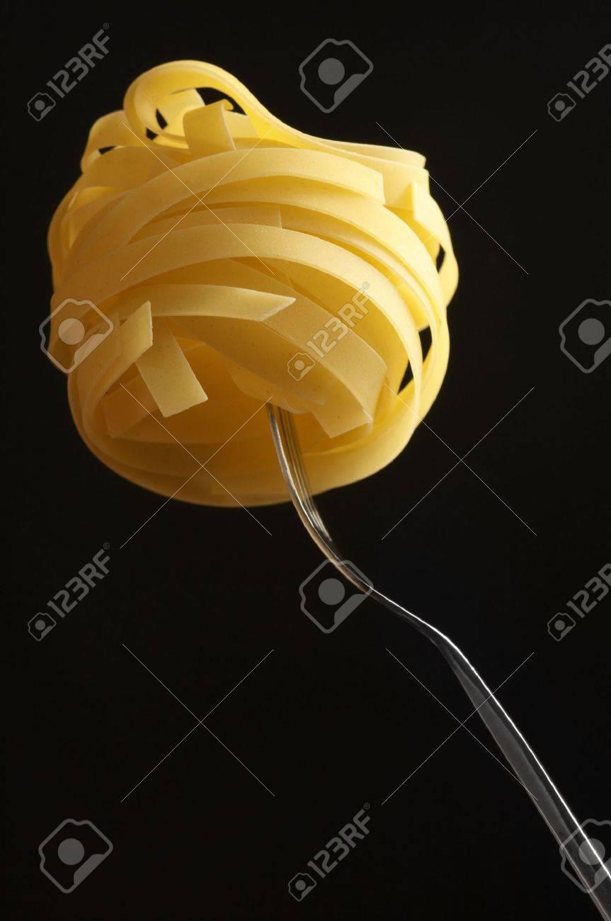 Raw pasta (tagliatelle) on fork against black background. Stock Photo - 6507764