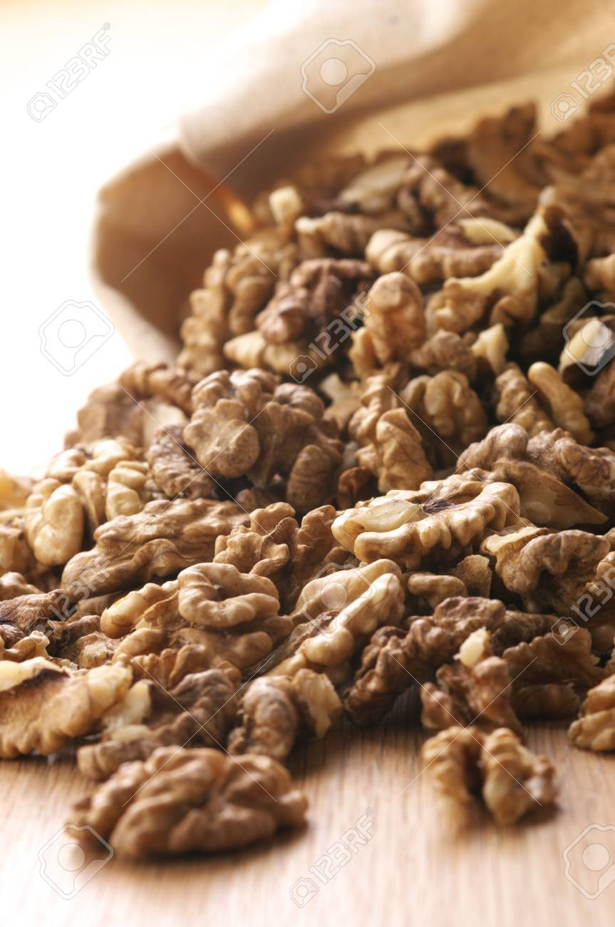 Heap of raw walnuts spill out canvas bag. Stock Photo - 6793341