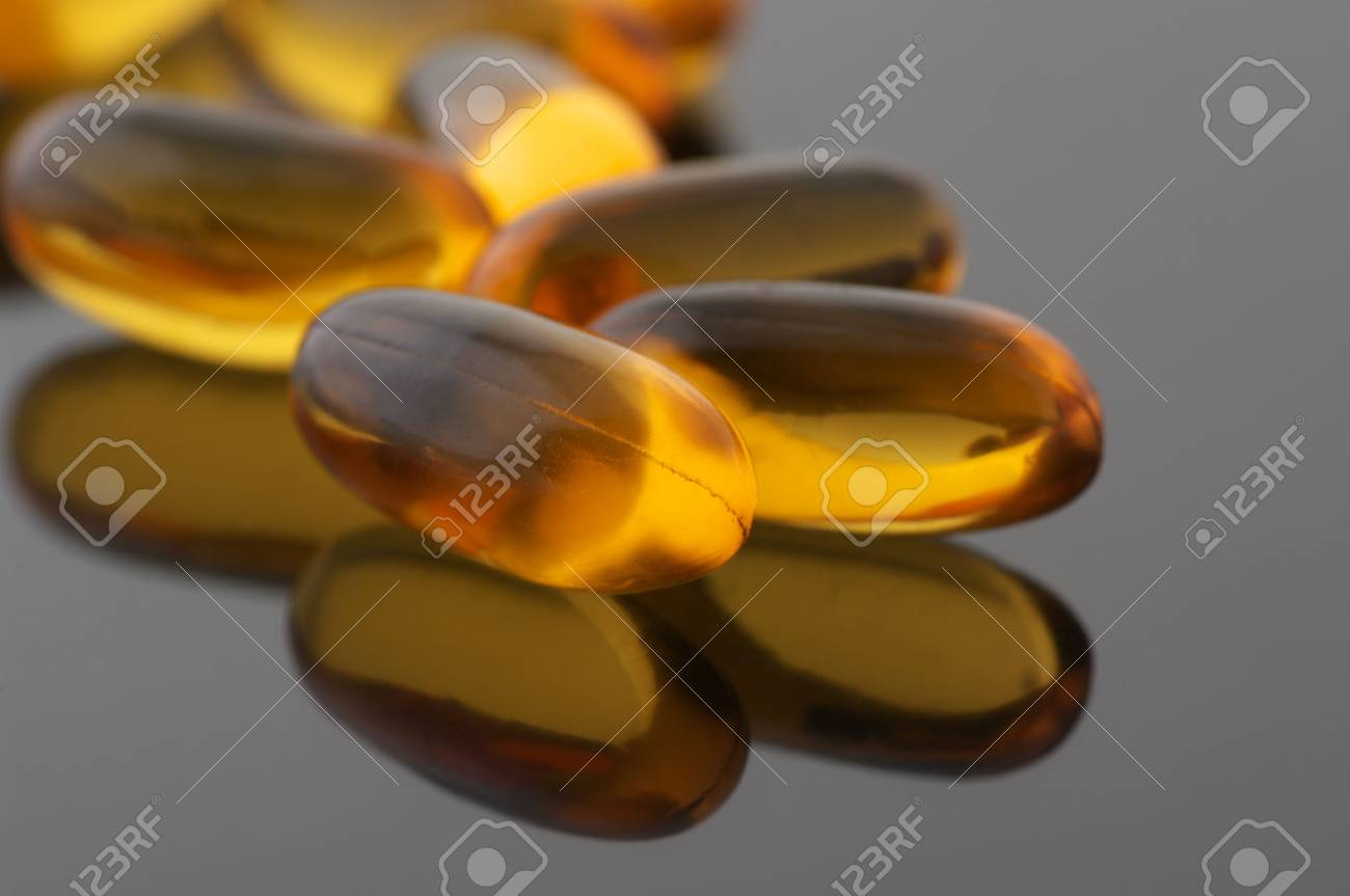 Capsules of cod liver oil on gray background with reflection. Stock Photo - 7218414