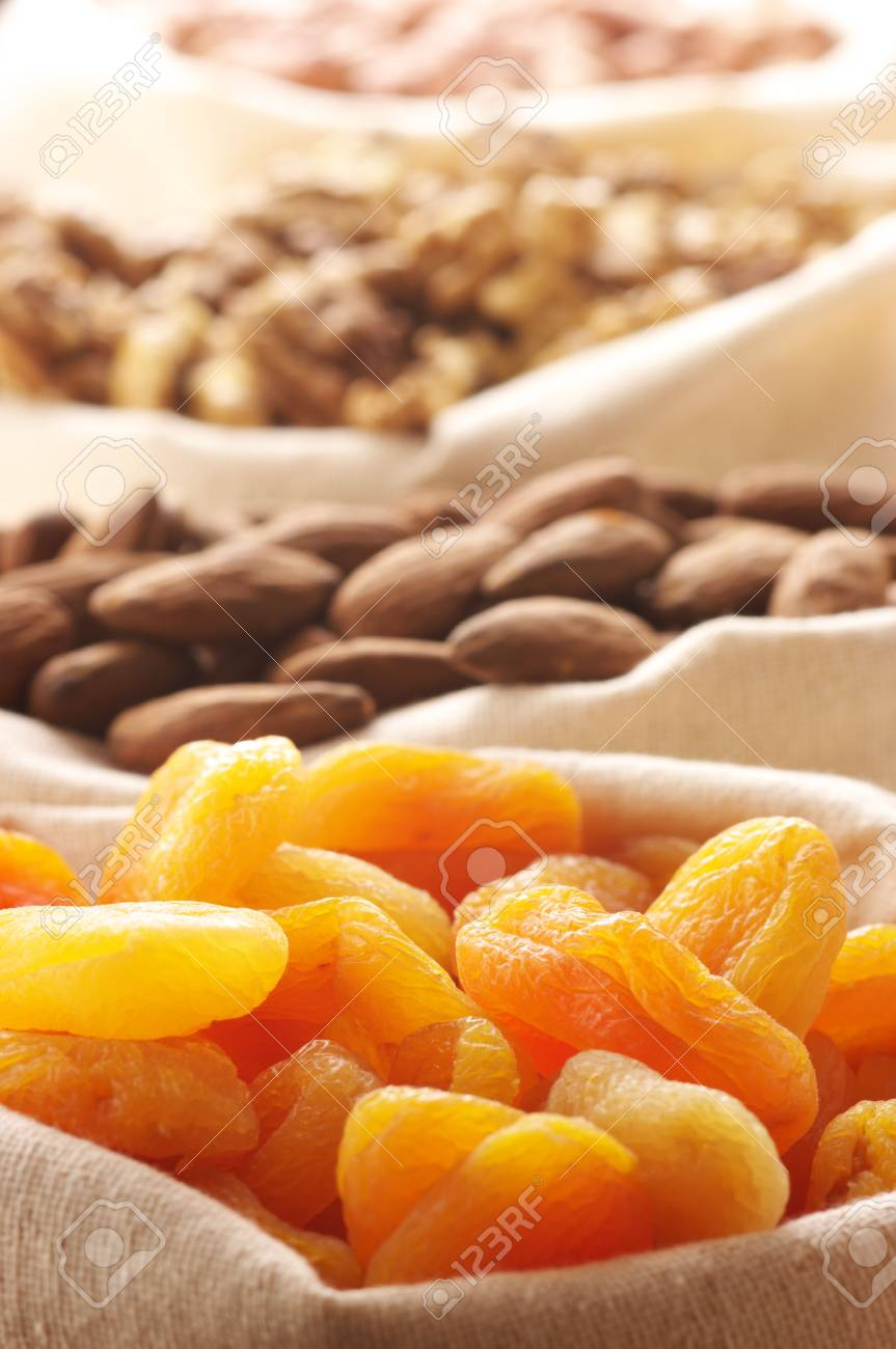 Heap of nuts and dried apricots in canvas bags. Focus on apricots. Stock Photo - 7749320