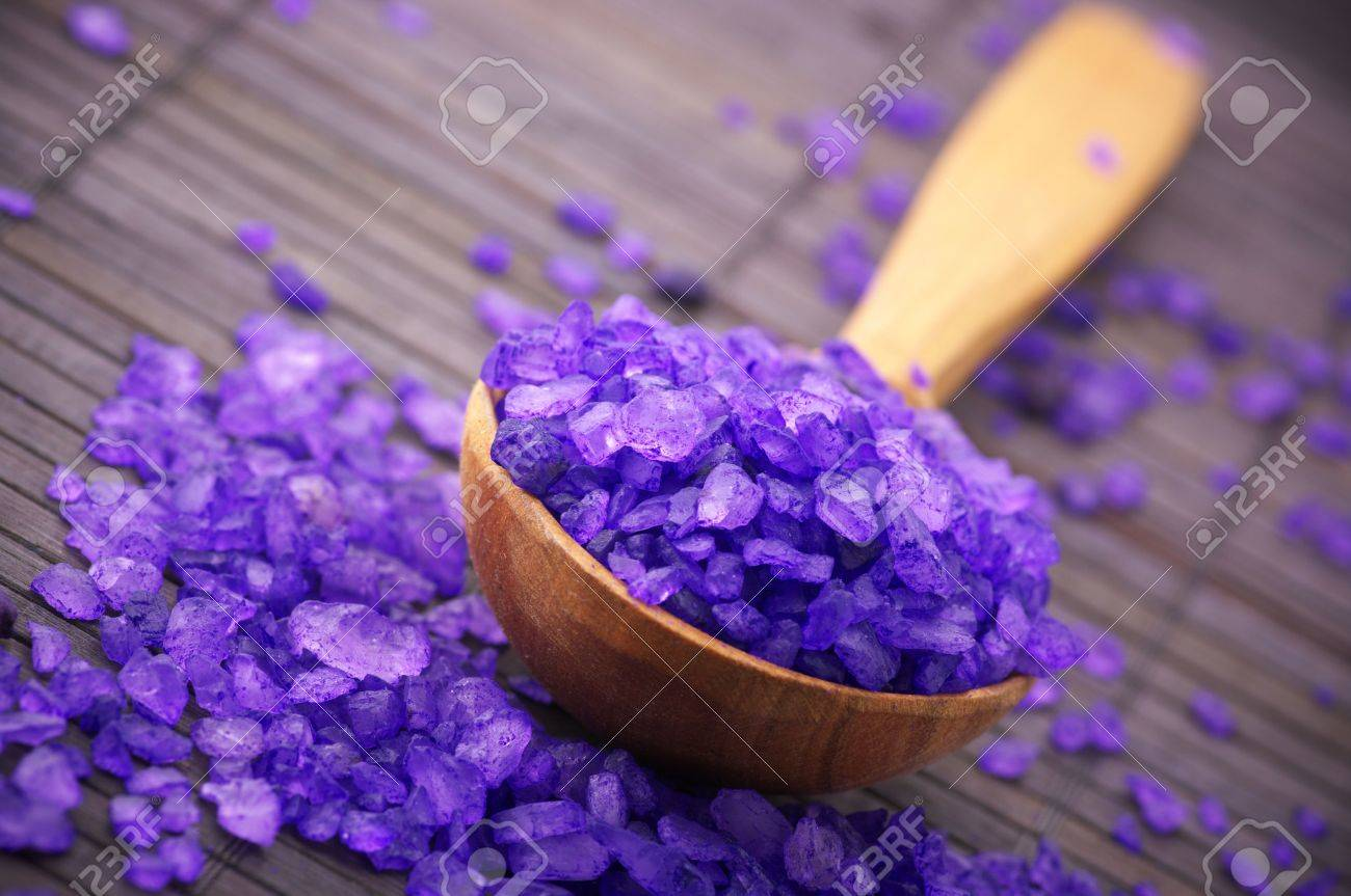 Close-up of violet bath salt in wooden spoon on brown mat. - 7749332
