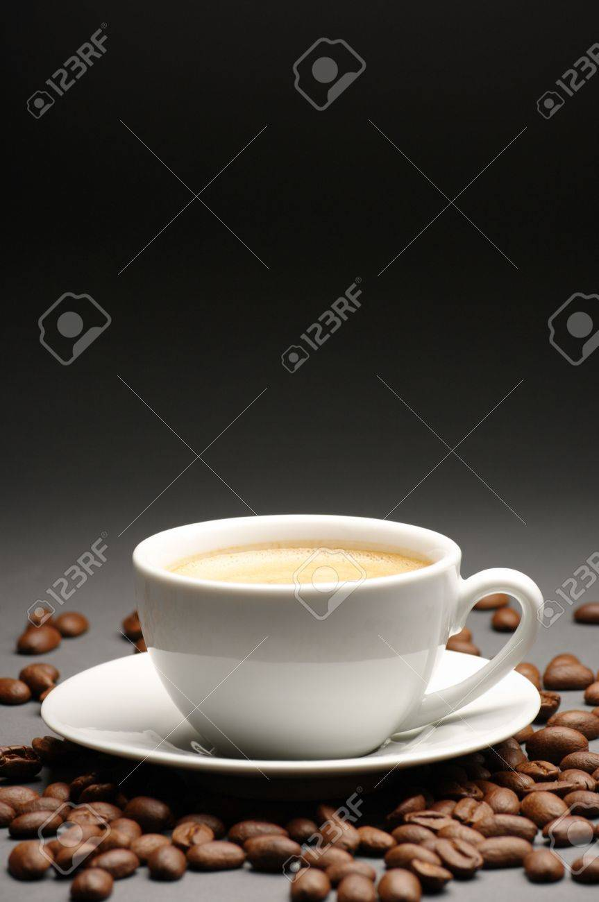 White cup of coffee with froth and coffee beans on dark gray background with copy space. Stock Photo - 7835820