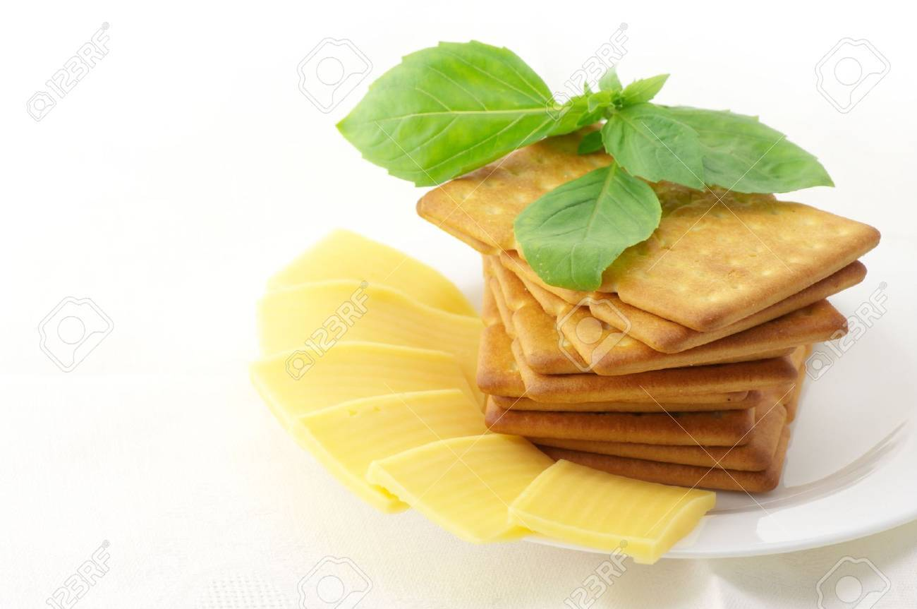 Stack of square crackers, slices of cheese and sweet basil in white plate on white background. Stock Photo - 7835844