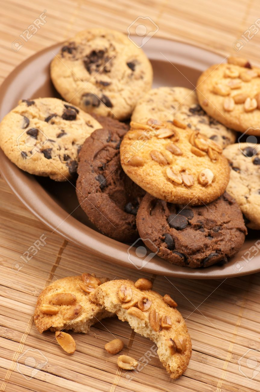 Plate of assorted cookies and broken cookie on mat. Stock Photo - 8080616
