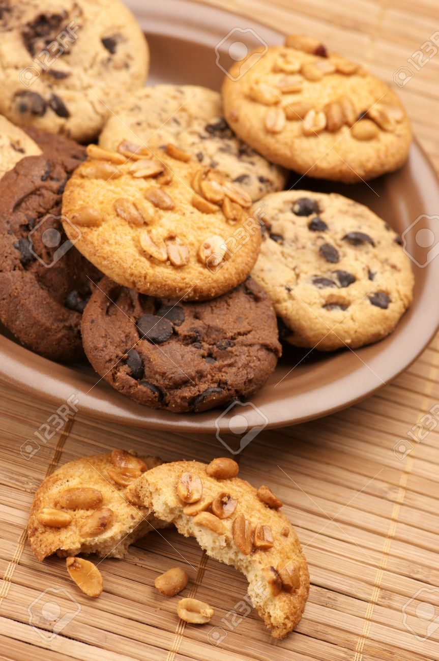 Plate of assorted cookies and broken cookie on mat. Stock Photo - 8612798