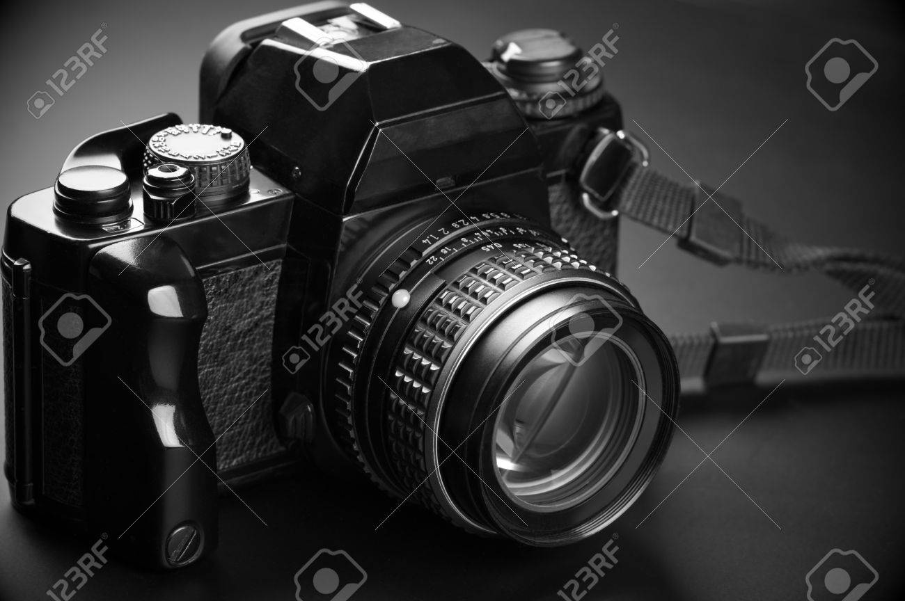Stock photo vintage mechanical 35mm film photo camera slr with manual focus normal lens on dark background black and white image