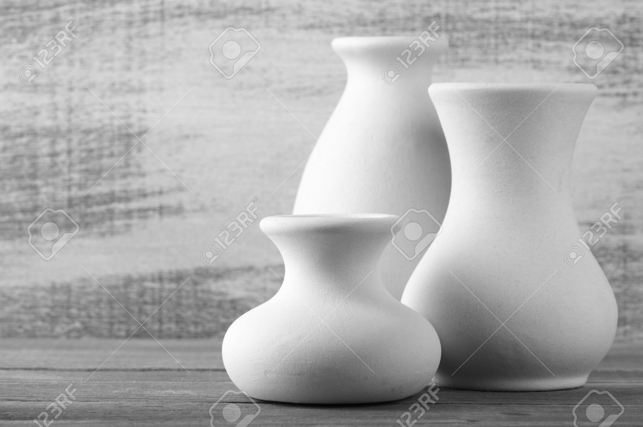 Three empty white unglazed ceramic vases on wooden table against three empty white unglazed ceramic vases on wooden table against rustic wooden wall black and reviewsmspy