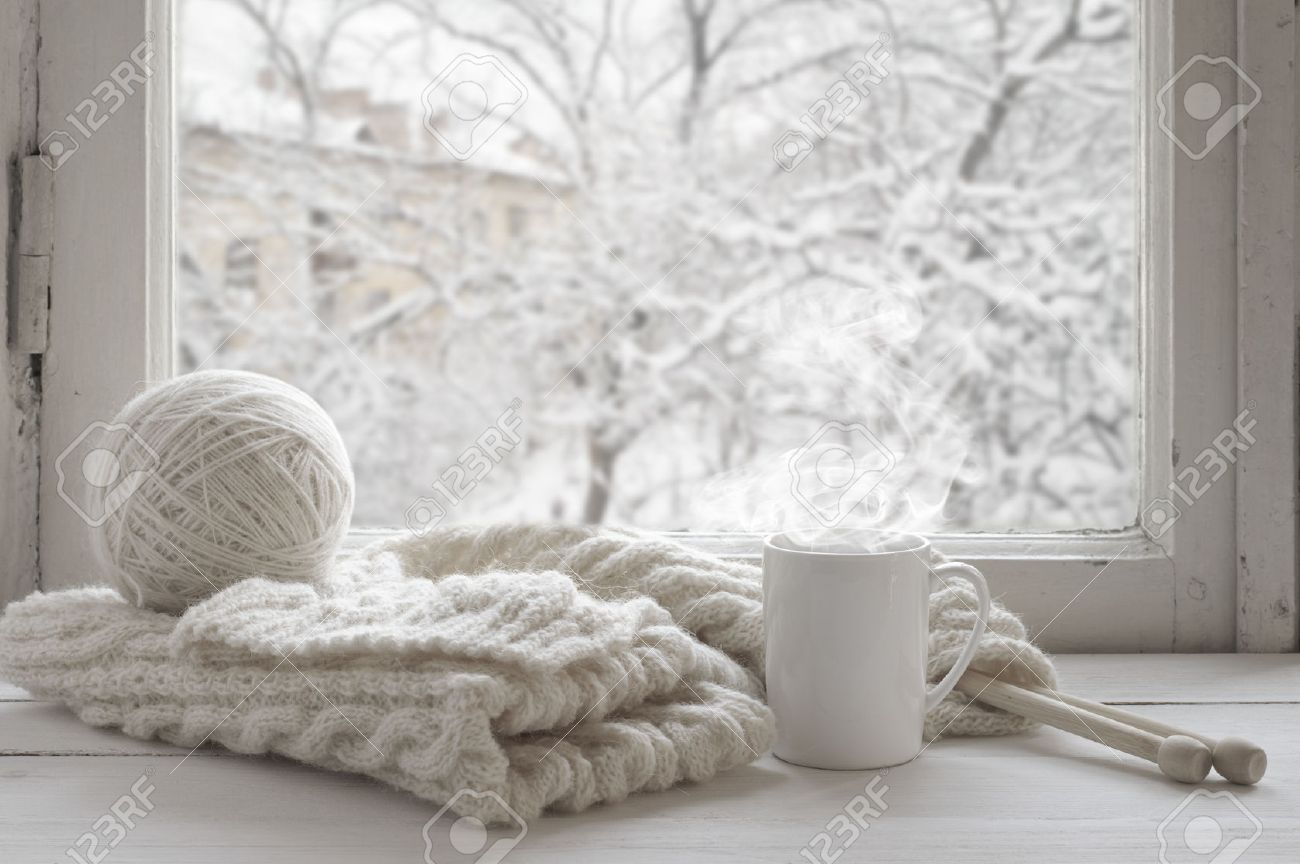 Cozy winter still life: mug of hot tea and warm woolen knitting on vintage windowsill against snow landscape from outside. - 47967113