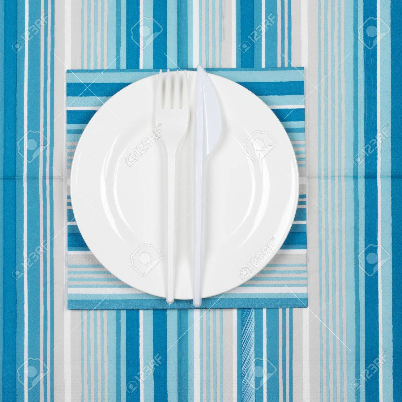 Disposable tableware set white plate with plastic fork and knife on blue striped paper napkins  sc 1 st  123RF.com & Disposable Tableware Set: White Plate With Plastic Fork And Knife ...