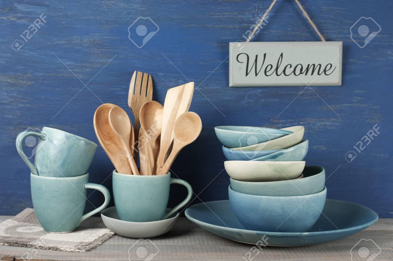 Banque Du0027images   Vaisselle Bleue à La Main Avec Des Ustensiles De Cuisine  En Bois Et Plaque De Bienvenue Contre Le Mur Peint Bleu Rustique.