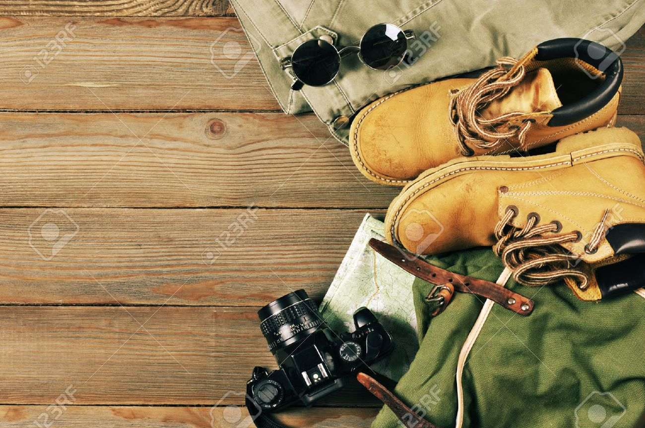 Travel accessories set on wooden background: old hiking leather boots, pants, backpack, map, vintage film camera and sunglasses. Top view point. - 55443913