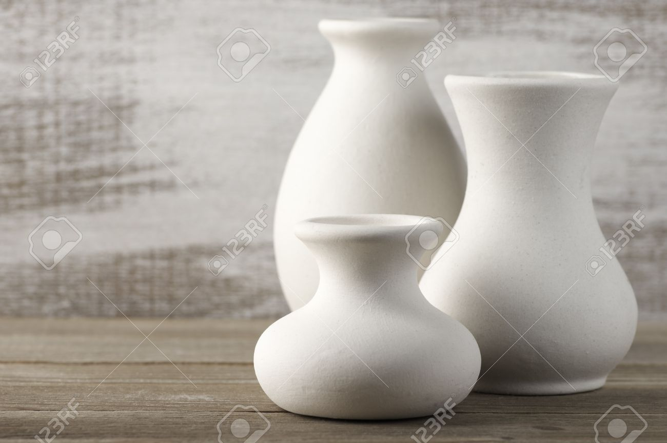 Three empty white unglazed ceramic vases on wooden table against three empty white unglazed ceramic vases on wooden table against rustic wooden wall shallow dof reviewsmspy