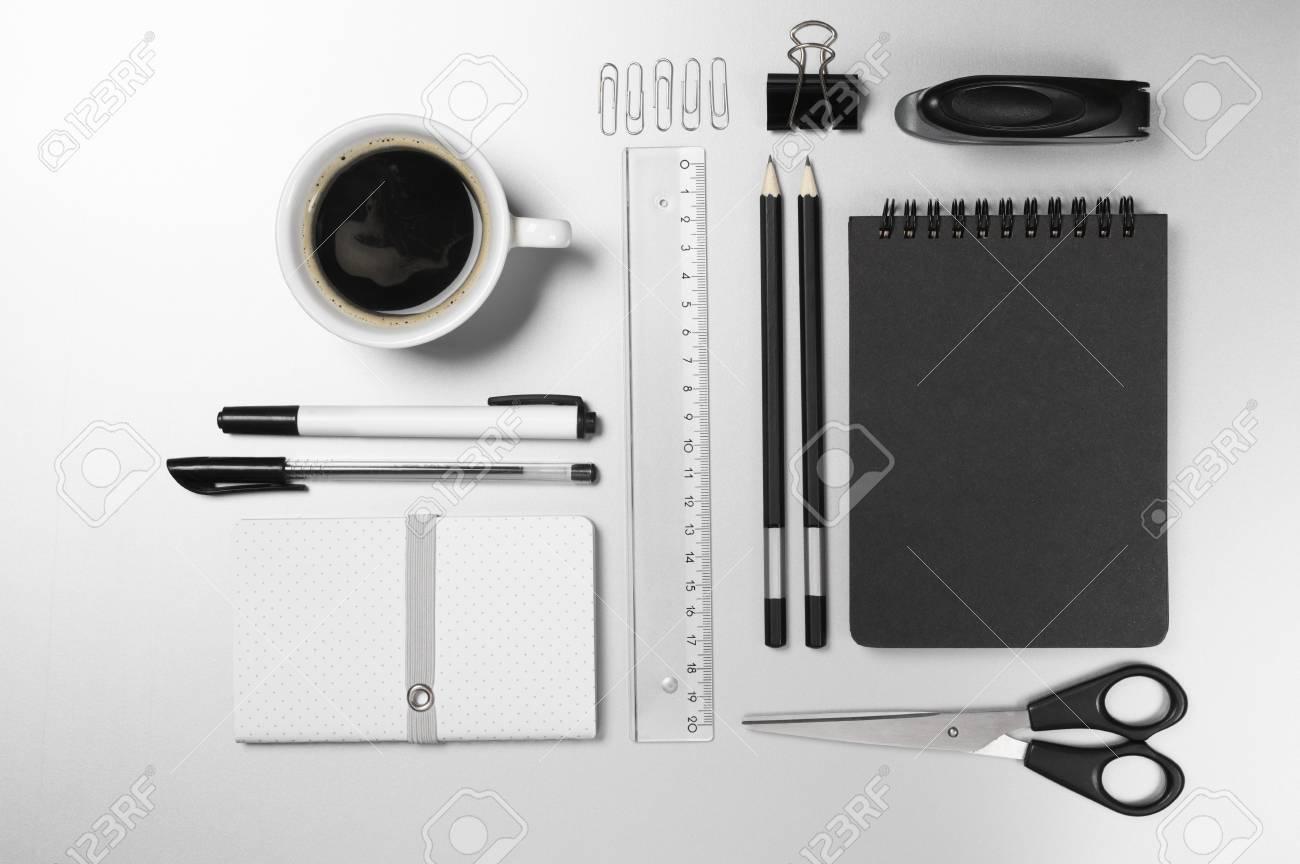 Papeterie noire et blanche sur un bureau gris: bloc notes crayons